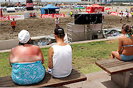 Woman with a sunburned back watches a football tournament on the beach. Often on the first day of their holidays the tourists from Northern Europe have a sunburn.