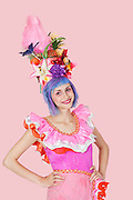 Portrait of beautiful young woman in Brazilian outfit over pink background