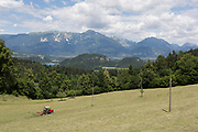 With Lake Bled and distant mountains of the Slovenian Alps and Austria further away, local farmer rakes grass on a hillside meadow, on 18th June 2018, in Kupljenik, Slovenia
