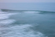 A long exposure blurs the motion of Pacific Ocean waves on a foggy morning in Venice Beach, California.
