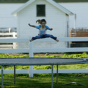 "land - columbus junction - july 3 -- Four year old Jade Woodsmall enjoys the trampoline on the farm her grandfather, Carl Stogdill works near Columbus Junction.  ""She's lived on the farm since before she was born,"" said grandmother Denise Stogdill.  ""I wish my children would have grown up on a farm.  I think it's good for a child's stability.""  photo by david peterson"