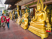 "12 NOVEMBER 2012 - BANGKOK, THAILAND:   People walk by Buddha statues for sale in a shop on Bamrung Muang Street in Bangkok. Thanon Bamrung Muang (Thanon is Thai for Road or Street) is Bangkok's ""Street of Many Buddhas."" Like many ancient cities, Bangkok was once a city of artisan's neighborhoods and Bamrung Muang Road, near Bangkok's present day city hall, was once the street where all the country's Buddha statues were made. Now they made in factories on the edge of Bangkok, but Bamrung Muang Road is still where the statues are sold. Once an elephant trail, it was one of the first streets paved in Bangkok. It is the largest center of Buddhist supplies in Thailand. Not just statues but also monk's robes, candles, alms bowls, and pre-configured alms baskets are for sale along both sides of the street.    PHOTO BY JACK KURTZ"