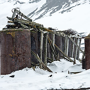 Metal tanks sit abandoned at the former Antarctic whaling station at Whalers Bay on Deception Island. Deception Island, in the South Shetland Islands, is a caldera of a volcano and is comprised of volcanic rock.