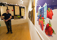 Huntington, New York, USA. February 20, 2014. A young man looks at paintings, including one of large strawberries, displayed at the Jingle Boom Holiday Bash, at the Main Street Gallery of Huntington Arts Council. Sparkboom, an HAC project, provides events such as this geared to Gen-Y, 18-34 years of age, to address the 'brain drain' of creative young professionals of Long Island. The paintings were the Annual Juried Still Life Show 'Inanimate.'