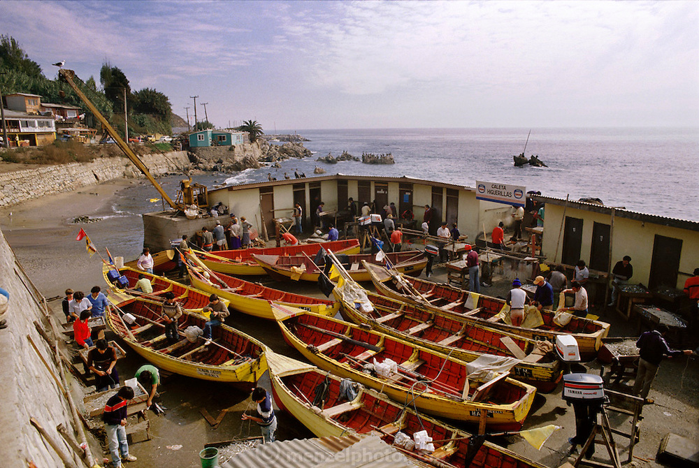 Fishermen work on their boats in the small protected harbor of Renaca, Chile.