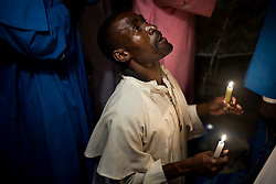 Elias Otieno prays with other members of the Legion Maria Church. Mathare, one of the poorest slums in Nairobi.  Running water and electricity are scarce and trash and human waste fills the streets.  Many people have no jobs and those who do work can earn less than one dollar a day.