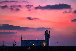 © Licensed to London News Pictures. 24/02/2018. Scarborough UK. The sky is turned pink at Dawn this morning behind the light house on St Vincent Pier in Scarborough as the UK prepares for the big freeze in the coming days. Photo credit: Andrew McCaren/LNP