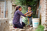 Local ENPHO staff member, Radhika Ghamire, teaching four year-old Rhythm Phuyal the technique for effective hand washing.