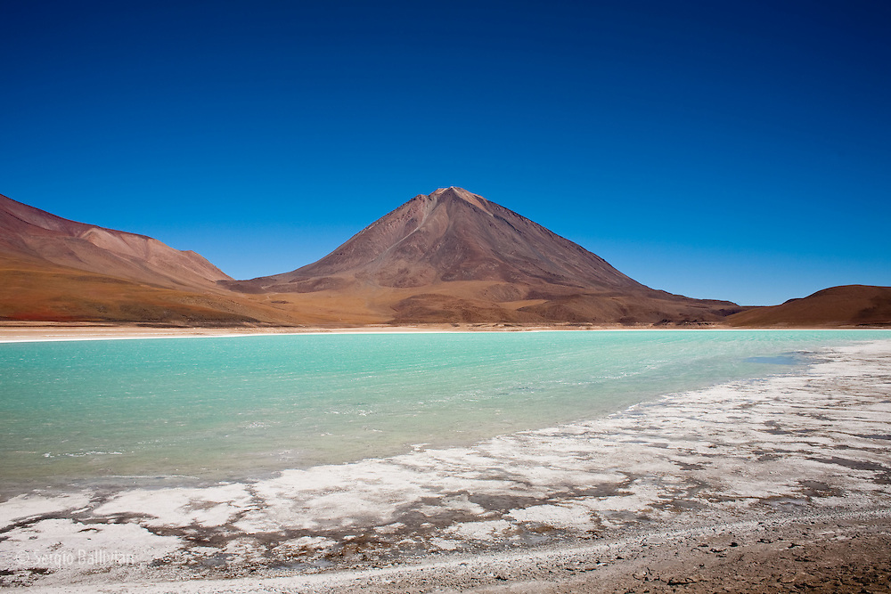 Laguna Verde sits at 14,500' above sea level, below the 20,000' Llicancabur Volcano deep in the Sud Lipez region of southwestern Bolivia.  The green color of the water comes from the natural leaching of minerals (like arsenic) from the surrounding mineral-laden peaks of the Andes mountains.