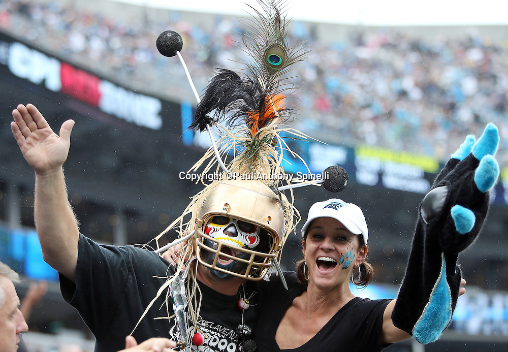 A New Orleans Saints fan and a Carolina Panthers fan cheer for their respective teams during the New Orleans Saints 2015 NFL week 3 regular season football game against the Carolina Panthers on Sunday, Sept. 27, 2015 in Charlotte, N.C. The Panthers won the game 27-22. (©Paul Anthony Spinelli)