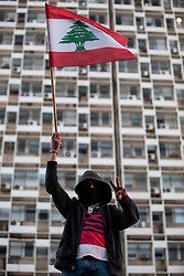 ©2020 Tom Nicholson. 11/01/2020. Beirut, Lebanon. A man waves the Lebanese flag outside 'Electricité du Liban', the main Lebanese electricity provider. Demonstrators are taking part in a protest march from Daoura in east Beirut to Parliament in Downtown Beirut. The demonstrations are part of a wider movement which started in mid October 2019, campaigning against government corruption and economic crisis. Photo credit : Tom Nicholson