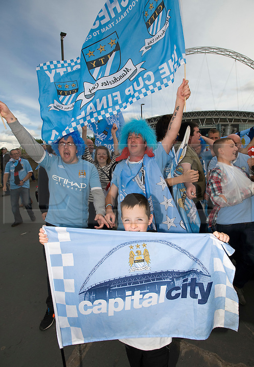 © licensed to London News Pictures. 14/05/2011. London, UK. Manchester City fans celebrate while leaving Wembley Stadium today (14/05/2011) after seeing their team win the FA Cup for the 5th time against Stoke City. Photo credit should read Ben Cawthra/LNP