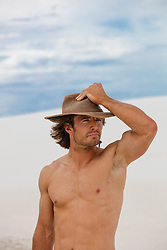shirtless man in the desert in an Outback hat