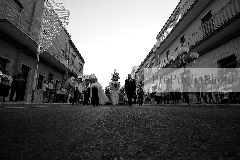 Ogni 15, 16, e 17 di luglio si festeggia a Mesagne (Br) la Madonna del Carmine, santa protettrice del paese. In fatti la storia narra che la Vergine abbia salvato la popolazione da un terribile terremoto nel 1700 circa. Questa foto ritrae i preti che sfilano in fila su i due lati della strada durante la processione che porta la statua della madonna verso la chiesa matrice. La foto è stata scattata il 15-07-2010.