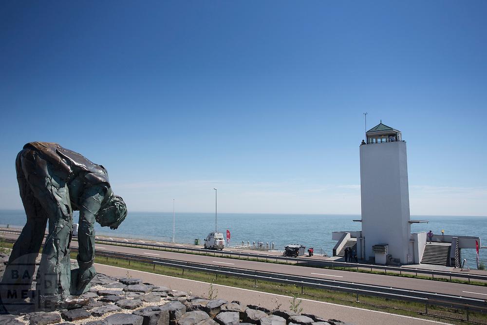 De Afsluitdijk bij het monument, met links het standbeeld van de dokwerker. Het is dit jaar tachtig jaar geleden dat de Afsluitdijk werd voltooid en de Waddenzee werd afgesloten van wat nu het IJsselmeer (op de foto) heet.<br /> <br /> In 1932, the gap between the Wadden Sea and the former Zuiderzee closed by the Afsluitdijk. Now it is a major thoroughfare between Friesland and North Holland and it separates the Wadden Sea from the IJsselmeer.
