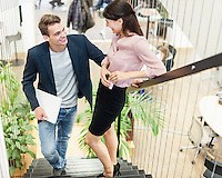 Full length of young business couple on staircase