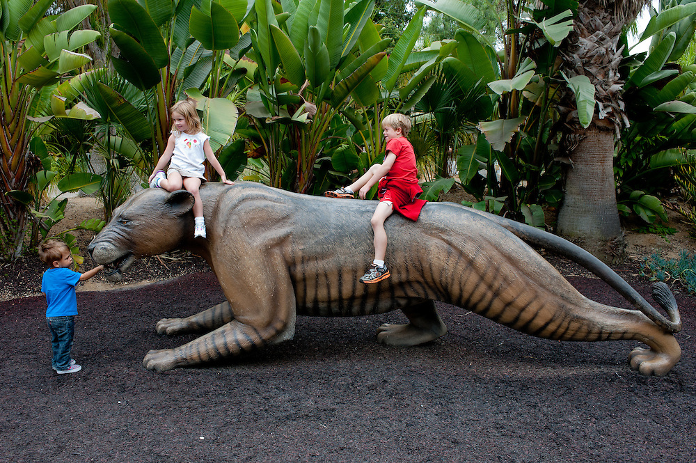 three young children riding on and playing with a giant model of an extinct tiger, at the San Diego Zoo