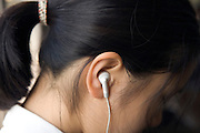 girl sitting in a Tokyo subway with headphones in her ears