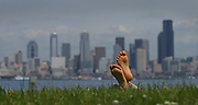 A sunbather relishes the warm sunshine at Alki in front of a backdrop of Seattle's skyline.<br />