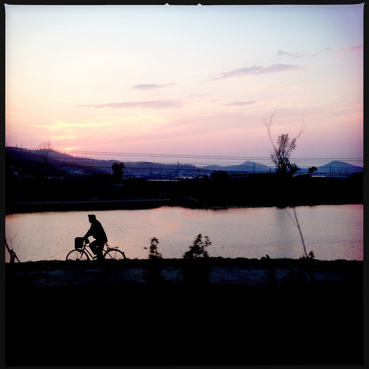 A man rides a bicycle at sunset in Pyongyang, North Korea.