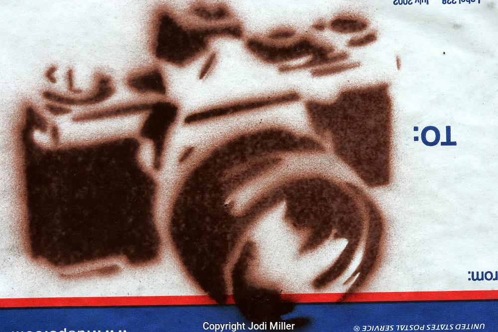Stencil art of a camera on a US postal service tag.