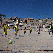 'Attitude at Altitude' Football in Potosi, Bolivia... Calvario score against and Galpes S.C. (yellow) team during the Liga Deportiva San Cristobal cup final on the stone and gravel surface high in the hills over Potosi, Calvario won the match 3-1. Potosi, Bolivia 9th May 2010..'Attitude at Altitude' Football in Potosi, Bolivia'..The Calvario players greet the final whistle with joyous celebration, high fives and bear hugs the players are sprayed with local Potosina beer after a monumental 3-1 victory over arch rivals Galpes S.C. in the Liga Deportiva San Cristobal. The Cup Final, high in the hills over Potosi. Bolivia, is a scene familiar to many small local football leagues around the world, only this time the game isn't played on grass but a rock hard earth pitch amongst gravel and boulders and white lines that are as straight as a witches nose, The hard surface resembles the earth from Cerro Rico the huge mountain that overlooks the town. .. Sitting at 4,090M (13,420 Feet) above sea level the small mining community of Potosi, Bolivia is one of the highest cities in the world by elevation and sits 'sky high' in the hills of the land locked nation. ..Overlooking the city is the infamous mountain, Cerro Rico (rich mountain), a mountain conceived to be made of silver ore. It was the major supplier of silver for the spanish empire and has been mined since 1546, according to records 45,000 tons of pure silver were mined from Cerro Rico between 1556 and 1783, 9000 tons of which went to the Spanish Monarchy. The mountain produced fabulous wealth and became one of the largest and wealthiest cities in Latin America. The Extraordinary riches of Potosi were featured in Maguel de Cervantes famous novel 'Don Quixote'. One theory holds that the mint mark of Potosi, the letters PTSI superimposed on one another is the origin of the dollar sign...Today mainly zinc, lead, tin and small quantities of silver are extracted from the mine by over 100 co operatives and private mining com