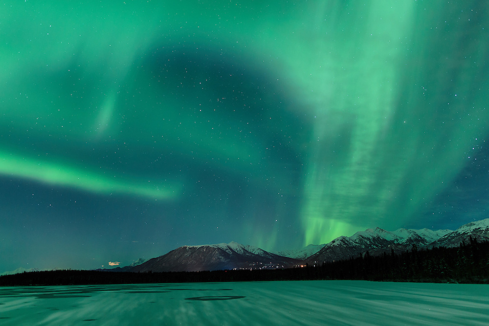 Aurora Borealis (northern lights) dance above Beach Lake in Chugiak with the Chugach Mountains in the background. Winter. Evening.