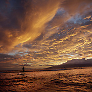 A surfer looks for his final wave of the day as the sun sets near Lahaina, Maui, in September of 2008.  In the distance is the island of Lanai.  With it's ideal climate and array of outdoor activities, Hawaii is one of the top travel destinations in the world.