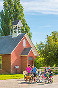 Families biking in downtown Albion near historic Albion Church built in 1888 in Albion, Idaho.