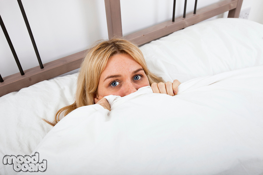 Portrait of young woman peeking over quilt