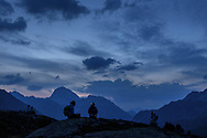 Zwei Frauen rasten in der Abendd&auml;mmerung bei den Crap Alv Laiets in der N&auml;he des Albulapasses mit Blick auf den Piz Ela, Parc Ela, Graub&uuml;nden, Schweiz<br /> <br /> Two women are resting at dusk at the Crap Alv Laiets close to the Albula Pass with the Piz Ela in sight, Parc Ela, Grisons, Switzerland