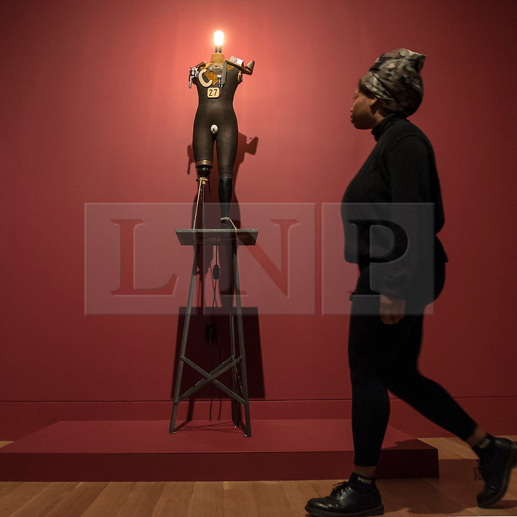 """© Licensed to London News Pictures. 04/06/2018. LONDON, UK. A gallery staff member views a reconstruction of """"The Petit-Bourgeois Philistine Heartfield Gone Wild (Electro-mechanical tatlin sculpture)"""", 1920, by John Heartfield and George Grosz at a preview of """"Aftermath:  Art in the wake of World War One"""" at Tate Britain.  The exhibition marks 100 years since the end of the First World War, exploring the impact of the conflict on British, German, and French art in over 150 works from 1916 to 1932.  The show runs 5 June to 23 September 2018.  Photo credit: Stephen Chung/LNP"""