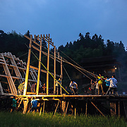At the crack of dawn, friends and family gather to help pull up a house that has been stacked in a pile by the master engineers. <br /> <br /> Shielded from the rest of Chinese civilization by a cascade of steep mountains, this village and the other surrounding lush villages have kept their Dong minority traditions and arts from centuries ago.<br /><br />With a history that goes back to the Tang dynasty, the area is adorned with stunning wooden Flower Bridges, bell towers and cascades of beautiful old houses. The Dong people have no written language, but use fine embroidery to communicate their love.<br /><br />Yet, as highways and tunnels plough through these mountains, the future of the village&rsquo;s 525 households is at crossroads. There is already a government blueprint to turn Dimen into a satellite town in the coming three years, as China embarks on its latest urbanization drive.
