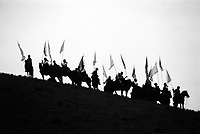 China, Hezhuo, 2007. Riders wait on the crest of a hill to join a massive display of horses and horsemanship at the Hezhuo Cultural Festival..