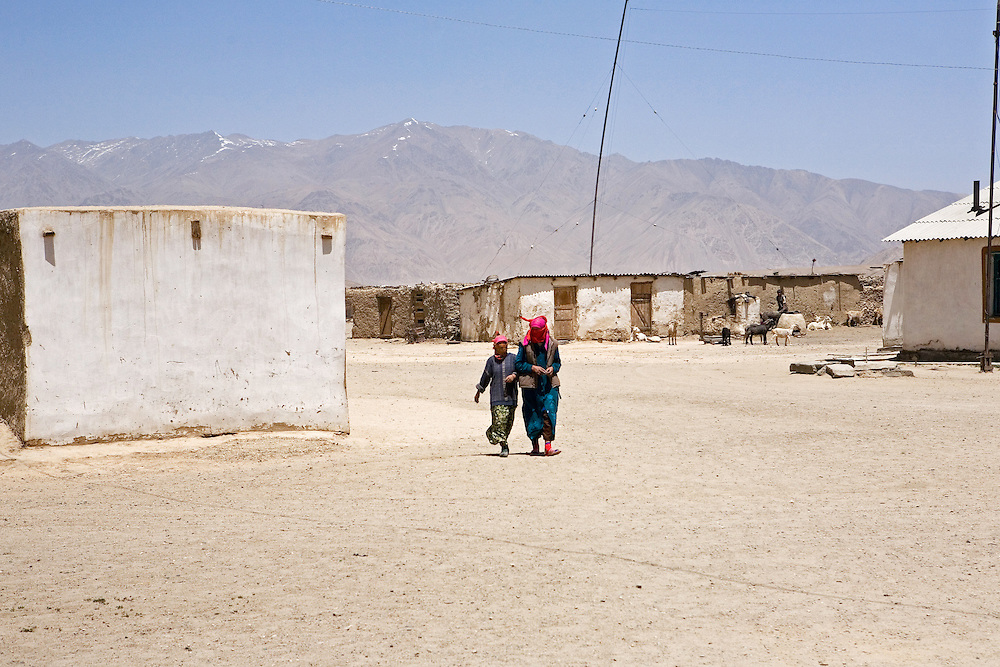 Women covered head to two for sun protection walk through desolate town of Bulunkul, Pamir plateau
