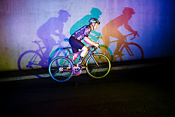 Cyclist Riding on Road casting Shadows on Wall