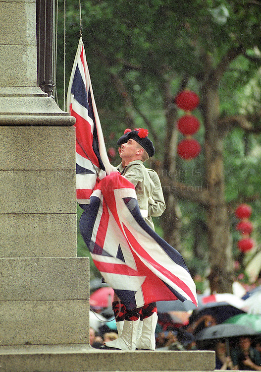 HONG KONG- JULY 1: Members of the British military take down the Union Jack flag for the last time from the Centopath in Central on June 30, 1997 in Hong Kong, China. On July 1, 1997 Hong Kong was handed over to China from the United Kingdom after being a colony for 150 years. (Photo by David Paul Morris) ..