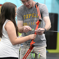 Bo Boatner works with Layla Stacy, 10, and her bow and arrow during Boatner's archery class at Lawndale Elementary School during the Tupelo Public School District's summer camps on Wednesday.