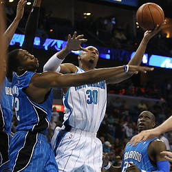 18 February 2009: New Orleans Hornets forward David West (30) shoots over Orlando Magic center Dwight Howard (12) during a NBA basketball game between the Orlando Magic and the New Orleans Hornets at the New Orleans Arena in New Orleans, Louisiana.