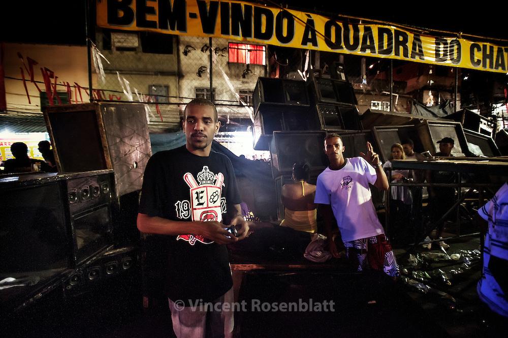 "Because of a brutal intervention of corrupted military police in the favela, the crowd of thousands of funkeiros fearing for their life - made collapse the soundsystem - of the mythical ball in the  favela Chatuba, Complexo da Penha. The favela  Chatuba is famous for having resisted to the assault of the Military Police for weeks, it also hosts one of the most famous and crowded bailes funk of Rio de Janeiro. As a song says, it's the ""Maracanã of Funk"", comparing the  Baile to the city's biggest football stadium.   The soundsystem is named after the favela: the  ""Chatubão Digital"", is commanded  by DJ Byano, one of the best in town, also famous for the quality of the funks he produces and their ""roots"" sound - here posing front of his destroyed soundsystem            ||                 Une intervention brutale de policiers militaires corrompus a provoqué un  mouvement de panique des milliers de funkeiros - et l'écroulement de l'Equipe de Som - le soundsystem. Baile mythique de la favela de Chatuba, Complexo da Penha. Connue pour avoir résisté des semaines victorieusement aux assauts de la police militaire, la favela de Chatuba abrite aussi un des plus fameux et bondé des Bailes Funk de Rio de Janeiro. Comme dit une musique, c'est le ""Maracanã do Funk"", comparant le Baile au plus grand stade de foot de la ville, et d'Amérique Latine. L'equipe de son porte le nom de la favela : c'est le ""Chatubão Digital"", commandé par DJ Byano, un des meilleurs de la ville, connu aussi pour la qualité et le son ""roots"" des funks qu'il produit - posant devant son ""Equipe"" détruite."
