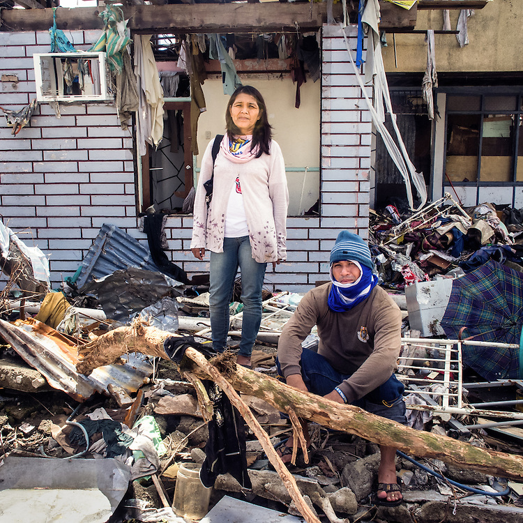 A portrait of husband and wife, Ronell and Lolita Rosales, standing where their home used to be before the typhoon.