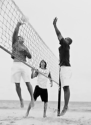 Three men playing a game of volleyball on the beach