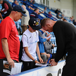 TELFORD COPYRIGHT MIKE SHERIDAN Telford boss Gavin Cowan stops to sign an autograph for a young Telford fan during the National League North fixture between AFC Telford United and Chester FC at the New Bucks Head on Saturday, September 14, 2019<br /> <br /> Picture credit: Mike Sheridan<br /> <br /> MS201920-018