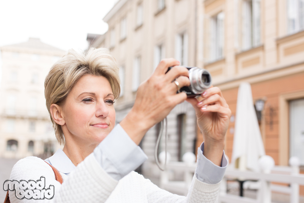 Woman photographing through digital camera in city