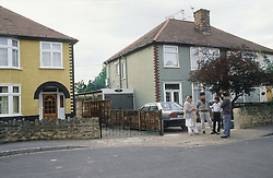 Family group standing on pavement outside semidetached house,