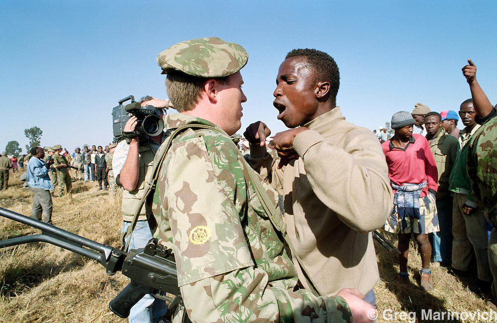An ANC supporting resident confronts a policeman who refused to allow residents to identify a person the police had shot and killed in the aftermath of President FW de Klerk's visit to the township where Inkatha Freedom party supporters killed  41 men women and children in Boipatong township, Vaal, June 1992.