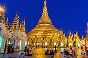 15 JUNE 2013 - YANGON, MYANMAR: Shwedagon Pagoda in the evening. The Shwedagon Pagoda is officially known as Shwedagon Zedi Daw and is also called the Great Dagon Pagoda or the Golden Pagoda. It is a 99 metres (325 ft) tall pagoda and stupa located in Yangon, Burma. The pagoda lies to the west of on Singuttara Hill, and dominates the skyline of the city. It is the most sacred Buddhist pagoda in Myanmar and contains relics of the past four Buddhas enshrined: the staff of Kakusandha, the water filter of Koṇāgamana, a piece of the robe of Kassapa and eight strands of hair fromGautama, the historical Buddha. The pagoda was built between the 6th and 10th centuries by the Mon people, who used to dominate the area around what is now Yangon (Rangoon). The pagoda has been renovated numerous times through the centuries. Millions of Burmese and tens of thousands of tourists visit the pagoda every year, which is the most visited site in Yangon.    PHOTO BY JACK KURTZ