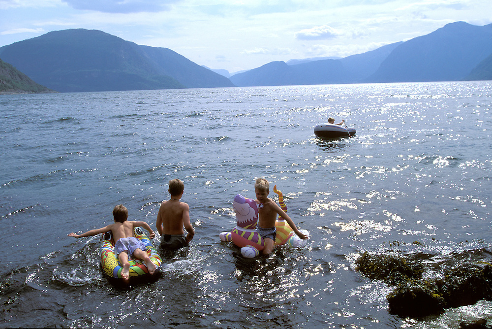 Europe, Norway. (MR) Family plays along the Sognefjord near town of Hermansverk, Norway
