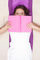 Directly above shot of woman covering face with book while lying on picnic blanket