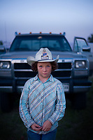 """Nine-year-old McKayla McCarville stands in the staging area outside of the Burwell arena where the 85th annual Nebraska's Big Rodeo is held. McKayla's father, Kirk McCarville, brought her to the rodeo and McKayla said that she nervously watched him compete in the rodeo's wild horse race. """"This may be a small town, but it's got a big rodeo, and it's got a really big heart,"""" 2013 Miss Burwell Rodeo Olivia Hunsperger said. In its 92nd year, the rodeo continues strong and serves as an economic stronghold for a small community in the Sandhills of Nebraska.   Chicago Freelance Photographer   Alyssa Schukar   Photojournalist"""